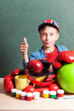 Funny schoolboy sitting at table with colorful school accessories Royalty Free Stock Photo