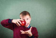 Funny schoolboy standing over a blackboard holding a big red apple Royalty Free Stock Images