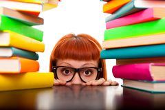 Funny schoolgirl. Peeking behind books and desk, isolated on white Royalty Free Stock Photos