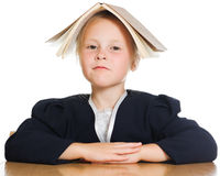 Funny schoolgirl sitting at a table Stock Photography