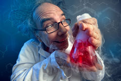 Crazy chemist lovingly looking at test tube stock photos
