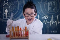 Funny scientist doing research in laboratory. Portrait of funny scientist doing research with chemical fluid and glassware Royalty Free Stock Image