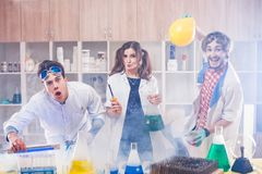 Funny scientists making experiment. Cheerful male and female funny scientists standing in smoke and making experiments in lab Royalty Free Stock Photography