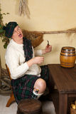 Funny Scotsman drinking whisky Royalty Free Stock Photography