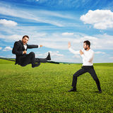 Funny screaming businessmen. In fight over green meadow and blue sky Royalty Free Stock Photo