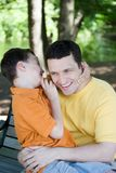 Funny secret. A boy is sharing a funny secret with his father Royalty Free Stock Photos