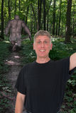 Funny Selfie, Bigfoot, Sasquatch. A man is hiking in the woods and comes upon Bigfoot or Sasquatch and takes a fun and funny selfie picture of himself Stock Photo