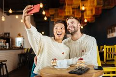 Funny young couple making selfie in coffee shop together. Funny selfie. Funny young couple wearing the same sweaters making selfie in coffee shop together stock photo