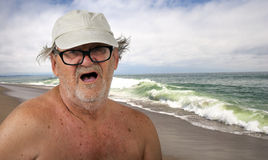 Funny Senior Citizen on the Beach. Male senior citizen comically enjoying his beach vacation. In the United States, elderly people visiting a warm southern Royalty Free Stock Photos