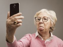 Funny senior lady taking selfies with toungue out stock images