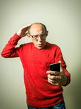 Funny senior man looking on phone Royalty Free Stock Photography