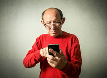 Funny senior man looking on phone Stock Images