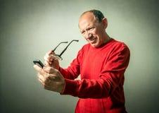 Funny senior man looking on phone Stock Photos