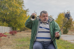 Funny senior man making faces while doing selfie. Outdoor Stock Photo
