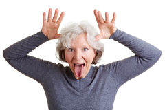 Funny senior woman showing her. Silly old senior woman showing her tongue and making a face Royalty Free Stock Photo