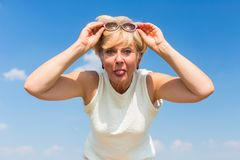 Funny senior woman sticking her tongue out while posing outdoors Royalty Free Stock Image