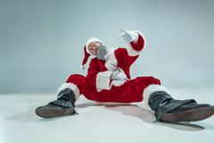 Funny guy in christmas hat. New Year Holiday. Christmas, x-mas, winter, gifts concept. Funny serious guy with christmas hat dancing at studio. New Year Holiday royalty free stock images