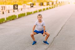 Funny seven-year-old boy in blue shorts and sneakers is on the pavement in the summer royalty free stock photography