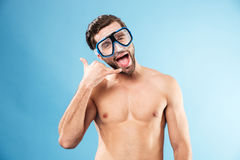 Funny shirtless man in swimming mask showing phone tube gesture Stock Photography
