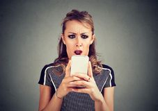 Funny shocked scared woman looking at phone seeing bad news photos message with disgusting emotion on face Royalty Free Stock Photography