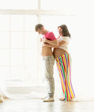 Funny shot of pregnant wife hugging husband with big abdomen Stock Image
