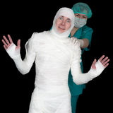 Funny sick in bandage and nurse on black. Funny sick in bandage and nurse isolated on black background Royalty Free Stock Image