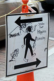 Funny sign. Pedestrian crossing sign states danger stinky feet hippies crossing, showing bare foot hippie crossing street with long hair and a joint and guitar Royalty Free Stock Image