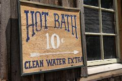 Funny sign for a Hot Bath Clean Water Extra for 10 cents on a rustic wooden abandoned building stock photo