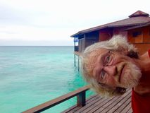 Funny silly older senior man with glasses photobombing tropical island holiday snapshot Royalty Free Stock Images