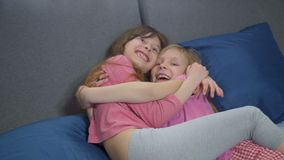 Funny sisters fooling around on bed. Two girls hugging and clinch each other. funny faces and pose stock video footage