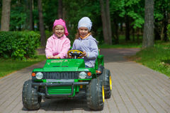 Funny sisters go to little green Stock Image