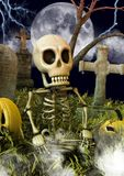 A funny skeleton sitting in a cemetery with Halloween pumpkins. royalty free stock photography