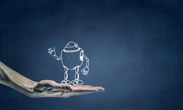 Funny sketched robot. Human hand holding in palm robot sketched model Royalty Free Stock Photo