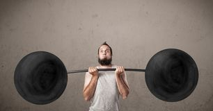 Funny skinny guy lifting weights. Funny skinny guy lifting incredible weights Stock Images
