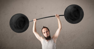 Funny skinny guy lifting weights Royalty Free Stock Images