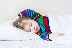 Funny sleeping toddler girl in a white bed Stock Photo