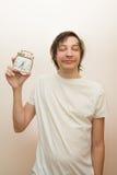 Funny sleeping white man hold mechanical alarm clock Stock Photo