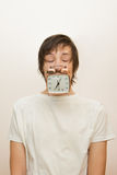 Funny sleeping white man hold in mouth alarm clock Stock Photography