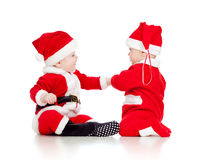 Funny small babies in Santa Claus clothes  Stock Photos