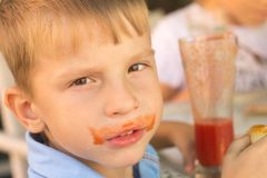 Funny small boy drinking tomato juice in cafe Royalty Free Stock Photography