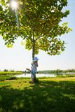 Funny small girl playing in the park, hiding behind the green tr Royalty Free Stock Photo