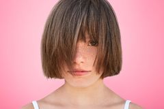 Funny small kid covers face with hair, demonstrates her new hairdo, feels like real model, poses against pink studio background. H. Eadshot of brunette little Stock Photography