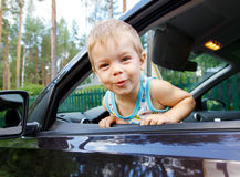 Funny small kid looking from open car window Royalty Free Stock Photos
