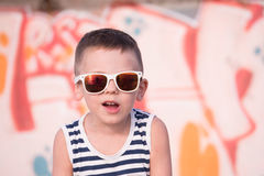 Funny small kid wearing sunglasses and shirt on graffiti background royalty free stock images