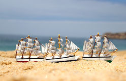 Funny small toy sailing ships on the beach Stock Images
