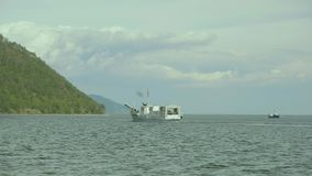 A small white ship floats in Lake Baikal near its coast in summer stock video footage