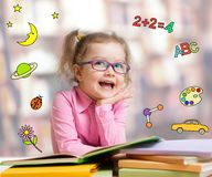 Funny smart kid in glasses reading book royalty free stock image