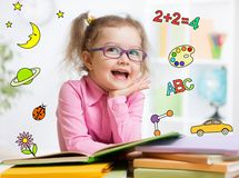 Funny smart kid in glasses reading book in. Kindergarten. Early education concept stock photography