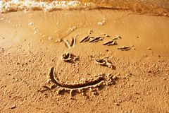 Funny smile face drawn in wet sand of beach Royalty Free Stock Image