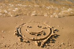 Funny smile face  on wet sand near sea Royalty Free Stock Photography